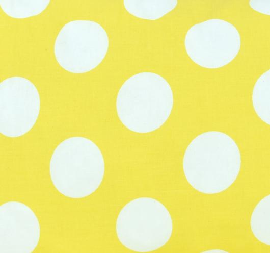 Ukrasni žuti jastuk s bijelim točkama.