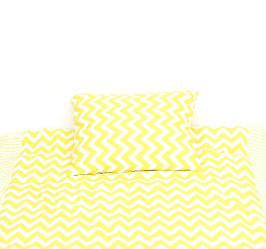 Posteljna garnitura sa žuto-bijelim cik-cak dezenom.